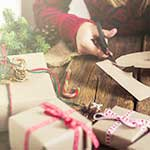 Woman adding a gift tag to holiday presents